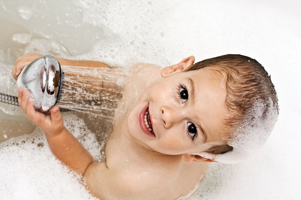 toddler standing in shower looking up at camera while playing with she shower head