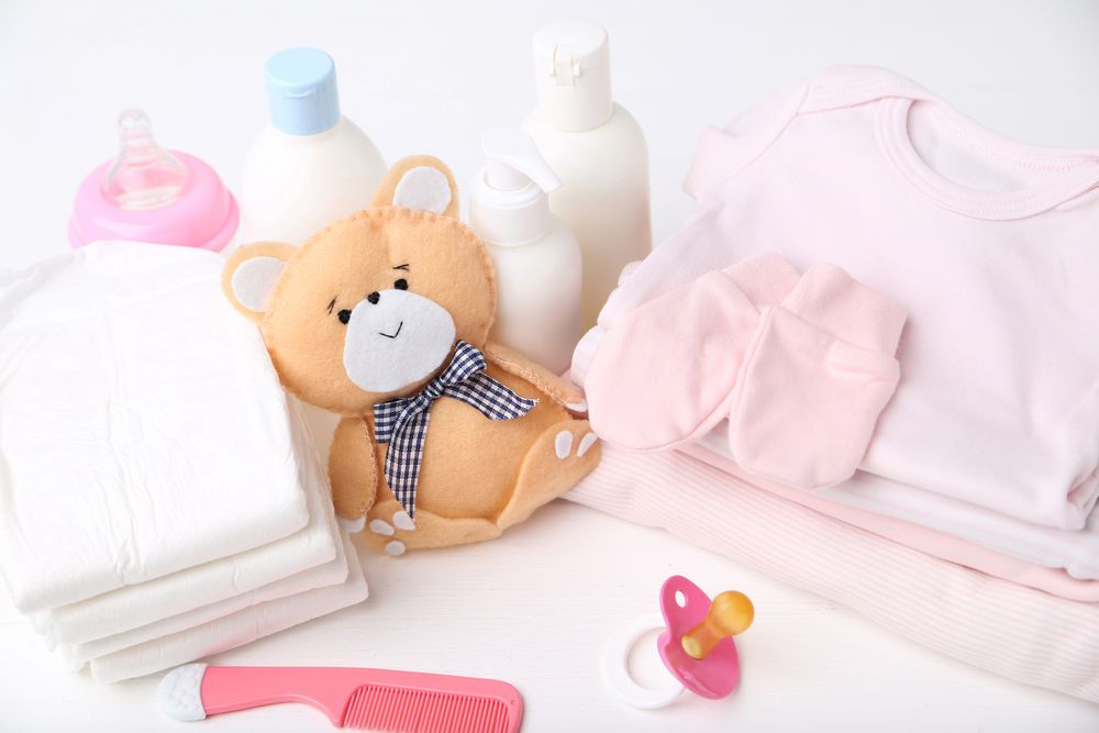 hospital freebies bundle with folded clothes, diapers, lotions, pacifier, and comb