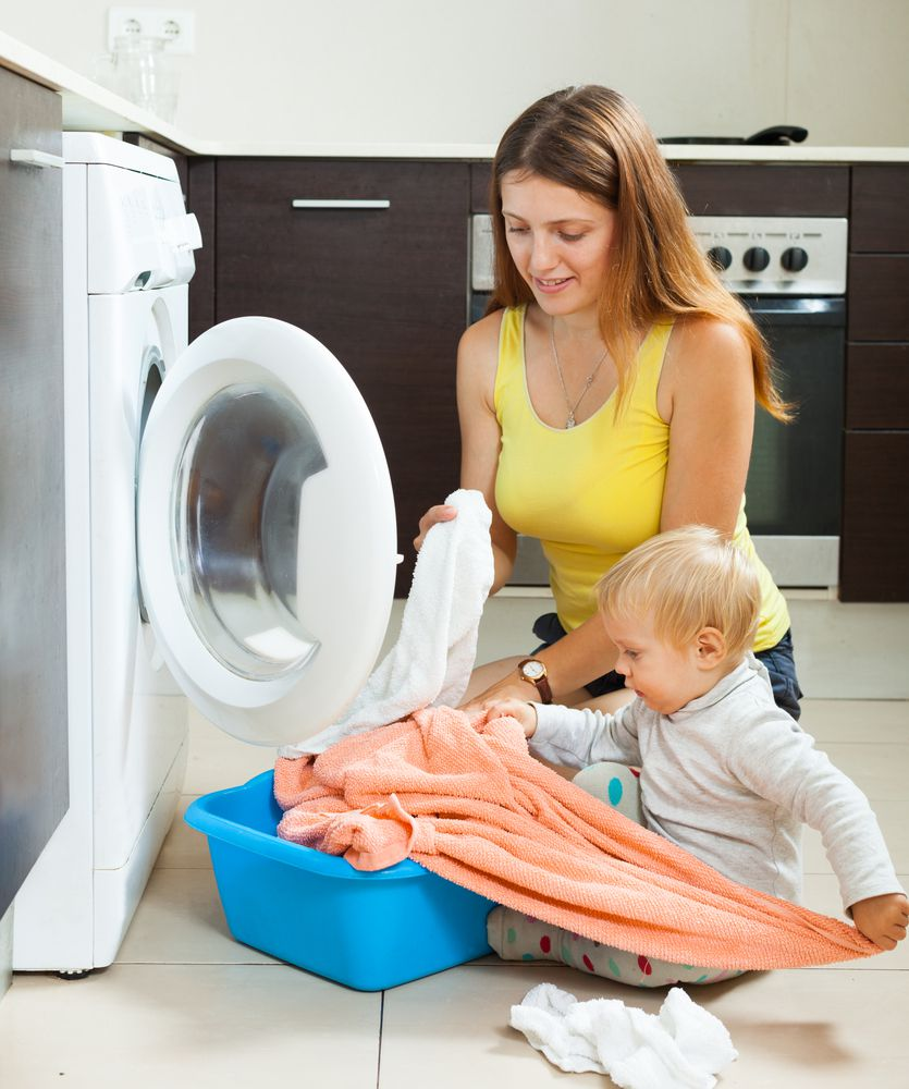 mom kneeling on the floor next to her baby while baby pulls laundry out of the basket and puts it in the washing machine