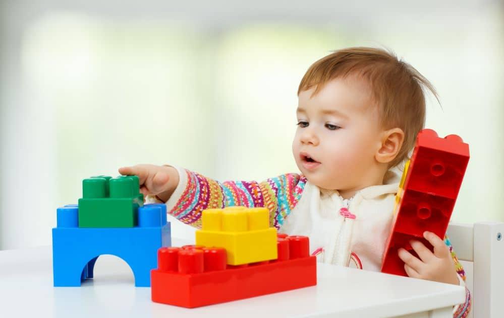 toddler sitting at table taking apart his lego toys