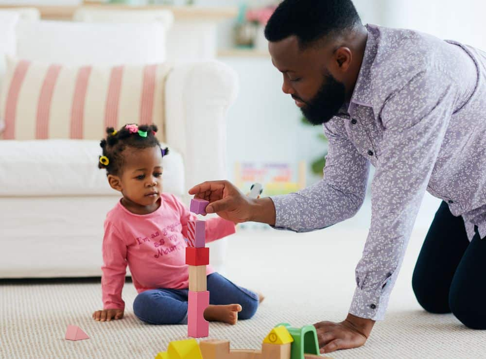 african american dad and daughter sitting on the floor building a tower with blocks and then taking apart their toys