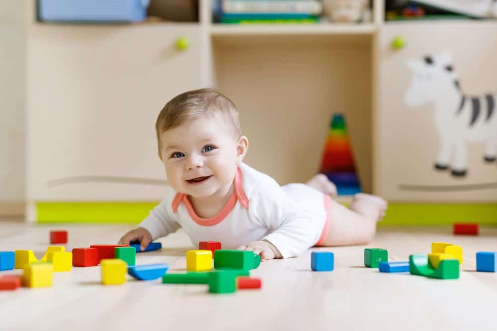 baby laying on the floor surrounded by blocks after tearing apart her tower